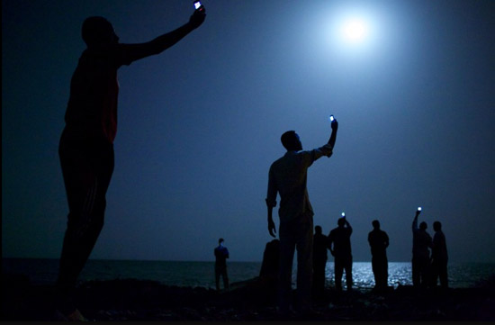SIGNAL 26 February 2013 African migrants on the shore of Djibouti city at night, raising their phones in an attempt to capture an inexpensive signal from neighboring Somalia—a tenuous link to relatives abroad. Djibouti is a common stop-off point for migrants in transit from such countries as Somalia, Ethiopia and Eritrea, seeking a better life in Europe and the Middle East.